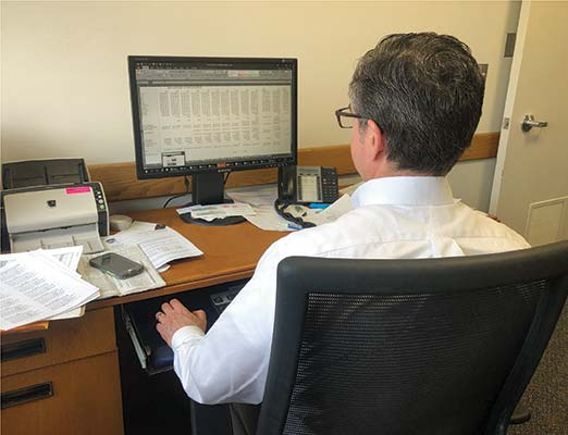 A Dane County employee looks at a spreadsheet