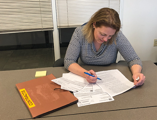 A Dane County employee signs a contract