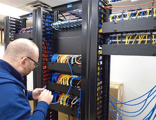 An Information Management employee works on wires